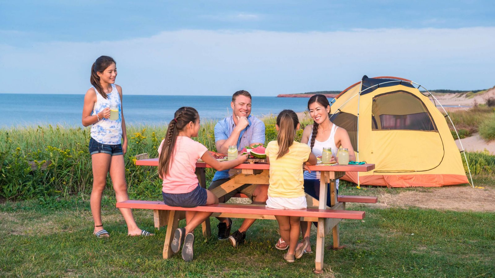Family at picnic table eating